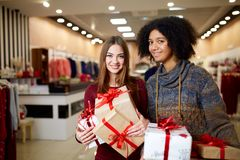 Two mixed race women with gift boxes in hands at store. Multi ethnic girls smiling with presents on christmas new year royalty free stock images