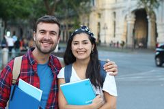Two mixed race students smiling outdoors royalty free stock photo