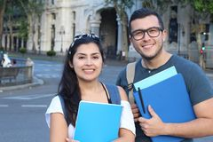 Two mixed race students smiling outdoors stock photography