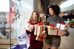 Two mixed race women with gift boxes in hands near storewindow. Multi ethnic girls smiling with presents on christmas royalty free stock images