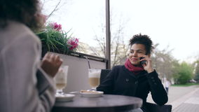 Two mixed race women sitting at the table in the street cafe, using smart phones and talking stock footage