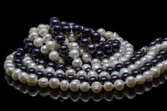 Two mixed strands of natural black pearl beads on a black background with reflection stock image