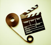 Two 35mm movie reels and clapperboard in vintage color effect Stock Image