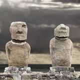 Two moai in Easter Island against grey sky. Two standing moai in Easter Island against cloudy grey sky stock photos