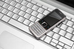 Two mobile devices. Wireless connect. Mobile phone on a silver laptop keyboard. Wireless connection Royalty Free Stock Photos