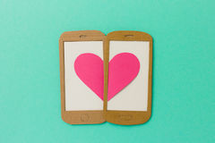 Two mobile phone screens combining a pink heart. Paper illustration image concept for online dating, flirting, chatting with space available for copy text Royalty Free Stock Image