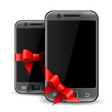 Two mobile phones with red gift ribbon Royalty Free Stock Images