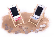 Two mobile phones in toy beach chairs. On the sand over white Royalty Free Stock Photos