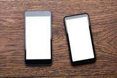 Two Mobile Phones On Wooden Desk. High Angle View Of Two Mobile Phones Showing Blank Screen On Wooden Desk Royalty Free Stock Images