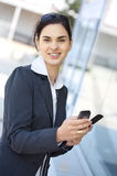 Two Mobiles. Young businesswoman is using two mobile phones at the some time. She is outdoor, somewhere in the downtown district Royalty Free Stock Photos