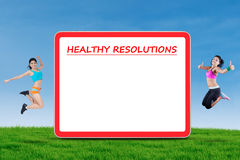 Two models and a board of healthy resolutions Stock Image