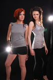 Two models in colorful setting in the studio. Two young models posing in the studio with backlights royalty free stock images