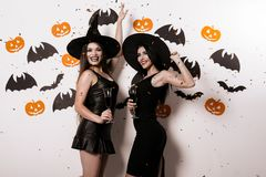 Two models are posing dressed in black sexy dresses and witches` hats. They smile Royalty Free Stock Photography