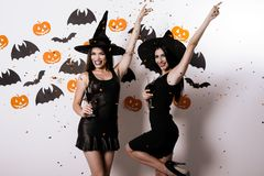 Two sexy models dressed in black witch costumes posing with their arms raised to the left Stock Photos