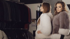 Two models posing in rich fur coats in boutique for advertising. In full HD stock video