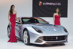 Two female models stand next to a Ferrari F12 Royalty Free Stock Image