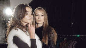 Two models stands in pose in fur coats in fashionable rich boutique stock video footage