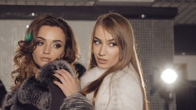 Two models stands in pose in fur coats in fashionable rich boutique. Slowly.  stock video