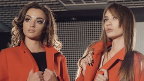 Two models stands in pose in the rich red coats for advertising. Slowly.  stock video footage
