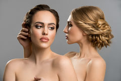 Two models topless embracing tenderly in studio. Two beautiful models with fine haistyles and make up posing together topless studio shot
