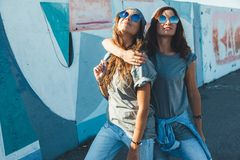 Models wearing plain tshirt and sunglasses posing over street wa. Two models wearing plain gray t-shirts and hipster sunglasses posing against street wall. Teen Royalty Free Stock Photos