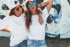 Models wearing plain tshirt and sunglasses posing over street wa. Two models wearing plain white t-shirts and hipster sunglasses posing against street wall. Teen Stock Photos