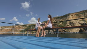 Two models in white dresses sitting on a bench on a pleasure boat in the sea. In slow motion stock video