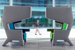 Two modern armchairs in waiting hall interior. Two modern empty armchairs in waiting hall with interior walking blury man in the background royalty free stock photography