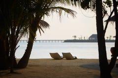 Two modern beach chairs on the beach. Indian ocean coastline on Maldives island. White sandy shore and calm sea. Travel. Beach chairs. Indian ocean coastline on stock photos