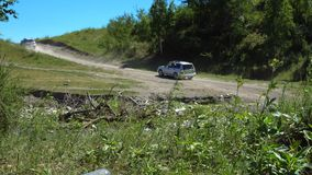 Two modern cars drive through mountainous terrain. Two modern cars drive along a dusty dirt road in a mountainous area. View from afar stock footage