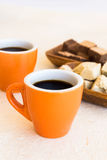 Two modern coffee cups with plates of sweets Royalty Free Stock Photo