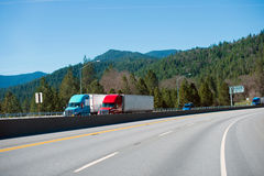 Two modern colored semi trucks driving highway turn side by side Stock Photo