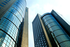 Two modern commercial buildings. Two high-rise glass and metal structure commercial buildings upward view stock photography
