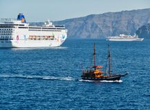 Cruise Ships, Santorini Caldera, Greece. Two modern cruise ships, and a twin masted old style sailing ship, a day cruise boat, in the Caldera, Santorini, a royalty free stock images