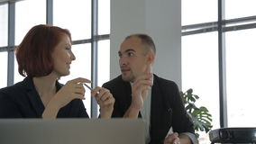 Two modern employee sitting next to the projector. At a business meeting, talking and working. a large bright spacious office with panoramic windows with green stock video