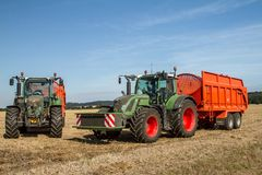 Two Modern Fendt tractors pulling orange trailers Royalty Free Stock Photography