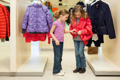 Two modern girls try on clothes in a store Royalty Free Stock Photo