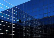 Two modern glass facades that intersect and reflect themselves. With shades of blue Stock Photos