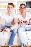 Two modern guys playing computer game holding controllers Stock Photo