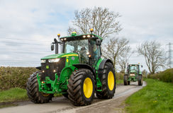 Two modern john deere tractors. On country road with lights on Stock Image