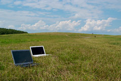 Two modern laptops on hillside Stock Photo