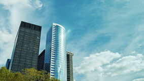Two modern office buildings against the sky and clouds drifting fast. The business district of Manhattan, USA. Glass skyscraper. High above the clouds float it stock footage