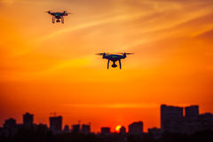 Two modern Remote Control Air Drones Fly with action cameras in dramatic orange sunset sk. Y. Cityscape silhouette in the background. Modern technologies. Kiev stock photos
