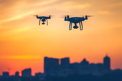 Two modern Remote Control Air Drones Fly with action cameras. In dramatic sunset sky. Cityscape silhouette in the background. Modern technologies. Close up royalty free stock image