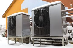 Two residential modern heat pumps. Two modern residential electric heat pumps buried in snow in winter Royalty Free Stock Photos