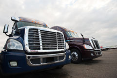 Two modern semi trucks on truck stop grills front view. Grilles and headlights of modern semi trucks like the eyes and mouth of huge monsters, bristling gloss Royalty Free Stock Image