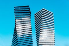 Two modern tall business skyscrapers with lot of glass windows against blue sky - Image stock photo