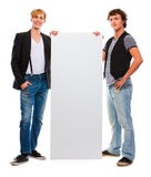 Two modern teenagers holding blank billboard Royalty Free Stock Image