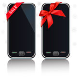 Two modern touch-screen mobile phones with ribbon Royalty Free Stock Photo