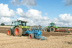 Two Modern tractors pulling ploughs Royalty Free Stock Photography
